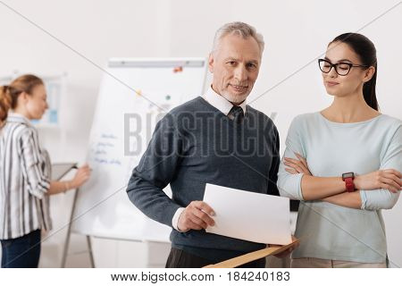 I will think. Handsome delighted male person keeping smile on face holding document in right hand while looking at camera