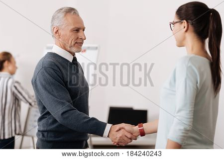 Shaking hands. Handsome man expressing positivity standing in semi position while looking straight at secretary