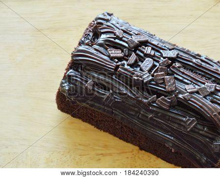 dark chocolate cake jam stuffed cream on wooden chopping block