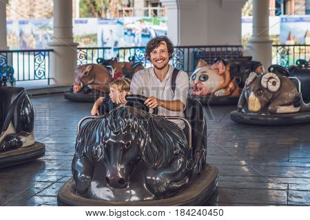 Father And His Son Having A Ride In The Bumper Car At The Amusement Park