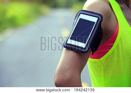 one woman runner wear armband listening music