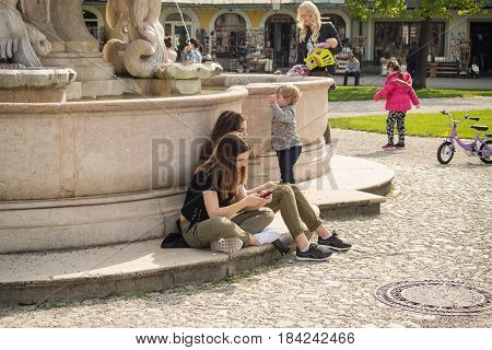 Altoetting,Germany-May 1,2017: Two girls write texts on their mobile phone while sitting on the steps of a fountain
