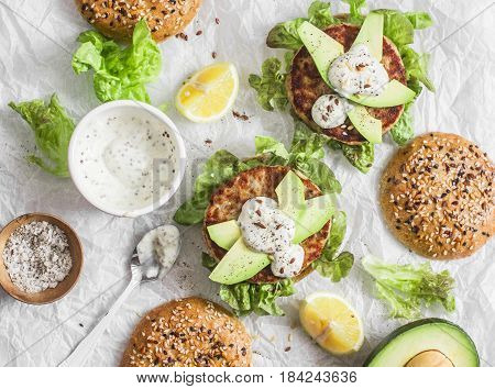 Tuna burger on a light background top view. Burger with tuna avocado and mustard sauce delicious appetizer or snack