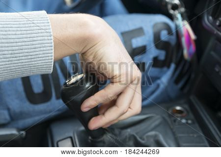 driver's hand lies on the shift knob, in the car's cab