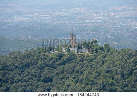 Close-up high angle view from observation deck of Temple of Sacred Heart of Jesus on Tibidabo mountain towards hill Turo del Puig and Sant Cugat del Valles town near Barcelona Catalonia Spain.
