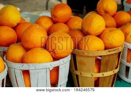 selling fresh organic oranges at farmer's market baskets