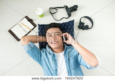 Top View Of Asian Man Lying On The Floor With Laptop, Camera, Tablet, Coffee Using Mobile Phone