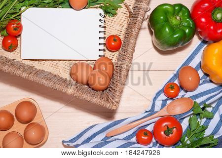 Open Recipe Book With Fresh Vegetables On Wooden Table.
