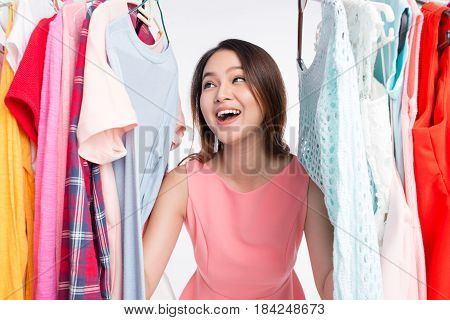 Young Asian Woman Surprised In Shop, Peeking Out Through Clothing In Clothes Rack