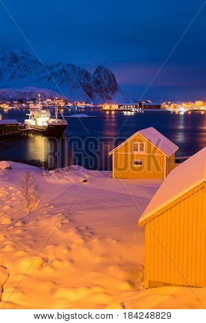 Fishing ship in the port of Reine with yellow houses in the foreground winter time