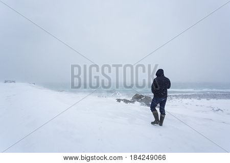 The lonely man is walking along the coast during the snowstorm