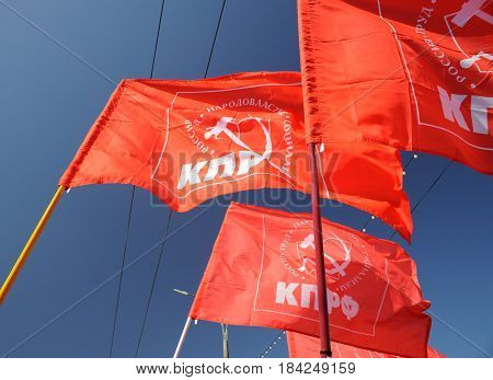 Orel Russia - May 1 2017: May demonstration. Red Communist flags against clear blue sky