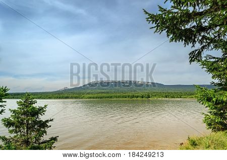 Mountain summer water landscape - lake and mountain range of Zyuratkul, Southern Urals, Russia. Mountain near the water in summer day-mountain lake in the frame of summer trees.Summer mountain nature with Zyuratkul lake-cloudy summer view