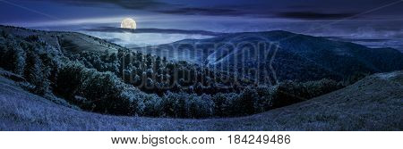panoramic summer landscape under dark sky with clouds. hillside meadow on Borzhava mountain ridge in Carpathians at night in full moon light