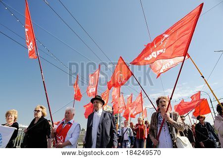 Orel Russia - May 1 2017: May demonstration. People marching with red Communist flags against clear blue sky