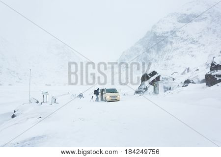 The photographer is traveling by the car on the Lofoten Islands during the blizzard