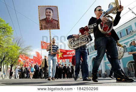 Orel Russia - May 1 2017: May demonstration. Trumpeters marching in front of crowd with Stalin portrait and red Communist flags background