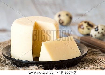 Round head of homemade cheese on a small plate on a burlap, next to quail eggs and a knife on a wooden table.