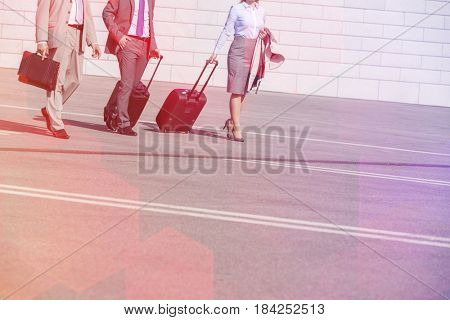 Low section of businesspeople with luggage walking on street
