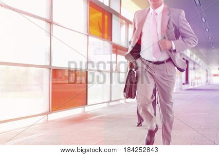 Midsection of businessmen rushing on railroad platform