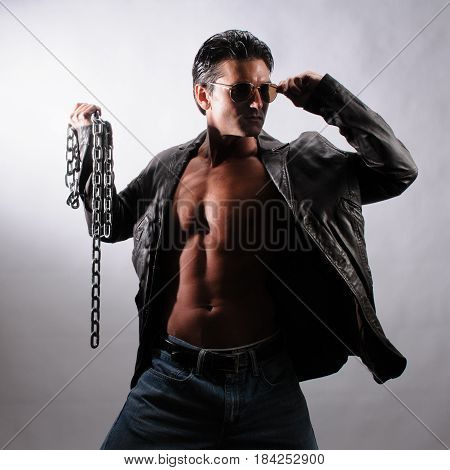 The sinister biker is holding a chain.
