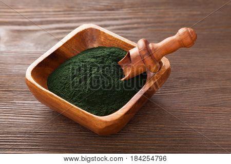 Ground Spirulina on wood background