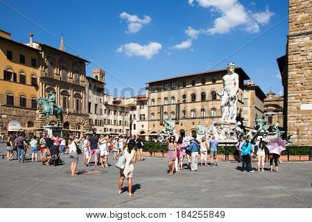 FLORENCE ITALY - July 28 2015: Piazza della Signoria or Signoria Square in Florence Italy taken during the summer and showing tourists the Fountain of Neptune and other historic statues and buildings. The square is a focal point of the city.