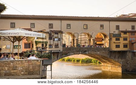 FLORENCE ITALY - July 28 2015: Diners and tourists sip wine along the Arno River in the shadow of the Ponte Vecchio Bridge in Florence Italy. The Ponte Vecchio is a medieval bridge famous for its shops and is a tourist destination spot in Florence.