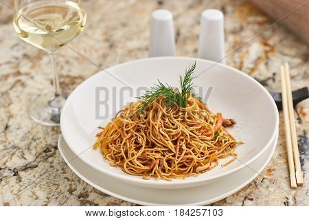 Thin egg noodles with vegetables and soy sauce served on white round plate with glass of white wine and chopsticks