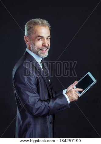 businessman with digital tablet on black background. the photo has a empty space for your text