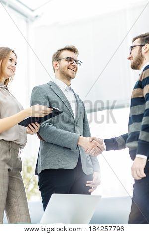 handshake business partners after discussion of the contract in a bright office.the photo has a empty space for your text.