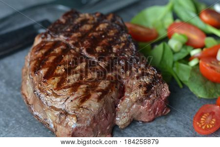 Close up of Barbecued Filet Mignon Steak. Nice grill marks showing and salad garnish.