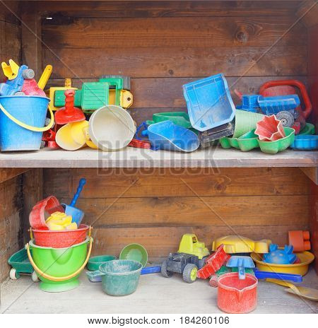 Childrens toys colorful plastic bucket spade and cars inside a praise