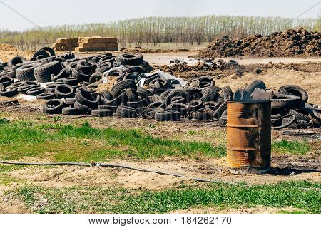 Landfill of old tires on the nature, iron round barrel burns, environmental pollution concept, copy space