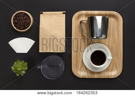 Top view of a black table with hand brewed coffee cup, bag, filter and brewing supplies. Top view with copy space.