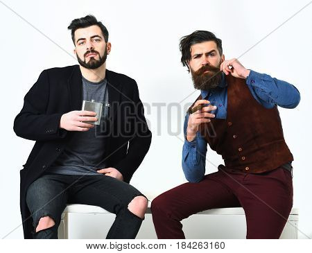 Two bearded mens short and long beard. Caucasian stylish hipsters with moustache holding flask with alcohol drink and cigar isolated on white background