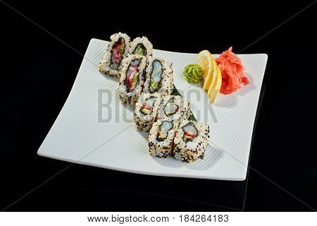 Sushi roll with scallop with vasabi, pickled ginger and lemon slice on white plate on black background