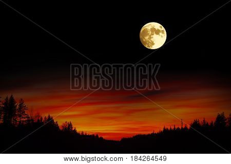 Landscape of sunset and a bright full moon in the night over the mountains. Astrotheme planets and starry sky. The scene with the round moon. The mystical nature time.