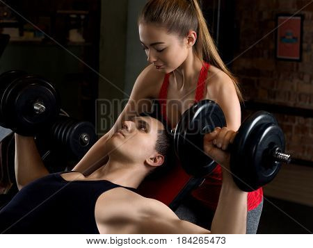 Man Lifting Dumbbells With His Personal Trainer