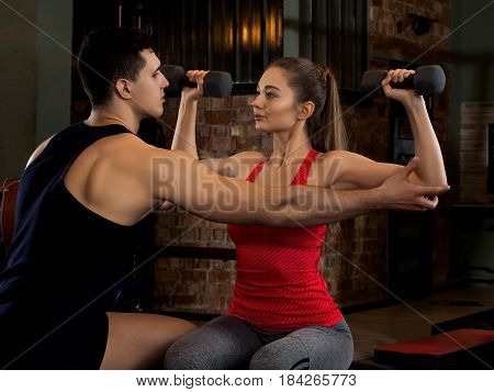 Woman Lifting Dumbbells With Her Personal Trainer