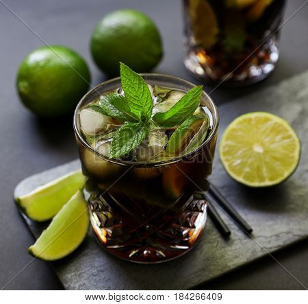 Cuba Libre or long island iced tea cocktail with strong drinks, cola, lime and ice in glasss, cold longdrink on dark background. Close-up.