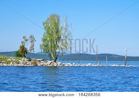 Summer water landscape - Gull Island on Turgoyak Lake , Southern Urals,Russia.Birch trees near the water in summer sunny day - summer nature landscape. Summer lake in the mountains -natural summer view. Colorful summer background