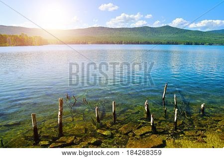 Colorful summer landscape of Turgoyak Lake in Southern Urals, Russia-the most transparent lake in the Ural mountains.Summer water mountain landscape -sun over mountains with clear water on the foreground.Summer nature.Summer mountain water landscape