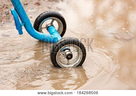 Children's bicycle wheels in a puddle on the road .