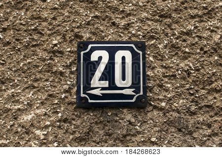 Weathered grunge square metal enameled plate of number of street address with number 20 closeup