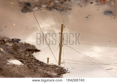 Electric pole reflected in a puddle on the road .