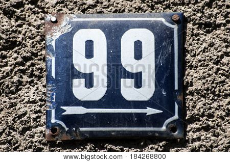 Weathered grunge square metal enameled plate of number of street address with number 99 closeup