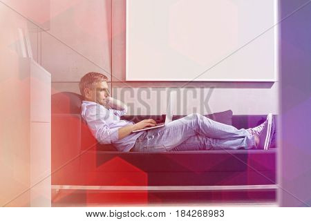 Full-length side view of Middle-aged man using laptop while lying on sofa