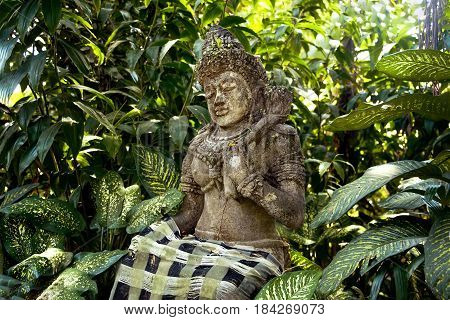 Ancient stone statue of an ancient deity on the island of Bali in a tropical forest among the trees