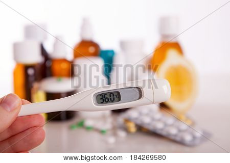 Group of medicines - bubbles drop pill thermometer - health theme. Hand holds a thermometer